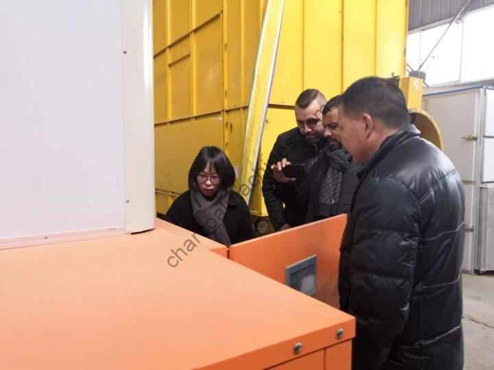 German clients examine the charcoal machine carefully